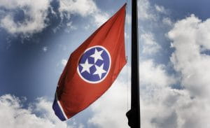 The Tennessee state flag, which features three white stars with five points inside a blue circle with a white outline in the centre of a horizontal red rectangle, and a vertical blue and white rectangle that flies opposite the flagpole.