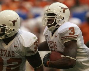 University of Texas player wearing a white uniform and helmet, with orange numbering, lettering, and logo, running with the football
