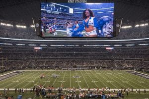 "AT&T Stadium which is the home-field of the Dallas Cowboys with their ""star"" logo at mid-field and ""COWBOYS"" painted in the end zones. The jumbotron above the field is the largest in the NFL and features on of the Cowboys' famous cheerleaders."