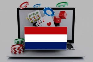 The Flag of the Netherlands in front of a laptop that represents online gambling, with chips, cards, and slot reels
