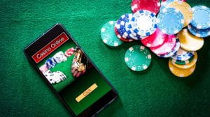 Smartphone with online casino imagery on the felt of a betting table next to poker chips