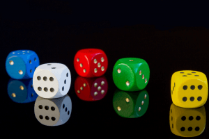 A reflection of five dices all in different colors. Blue, white, red, green and yellow