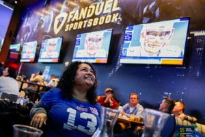 Woman in a New York Giants jersey at a New Jersey sportsbook during the Super Bowl with Tom Brady on the TV screens.