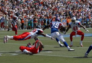 Running back Adrian Peterson in a blue uniform rushes with the football against the defensive players wearing white uniforms