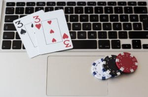 A pair of threes and four poker chips on a MacBook keyboard to represent online poker.