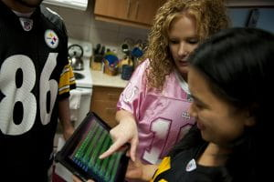 Daily fantasy sports bettors making selections while wearing NFL football jerseys