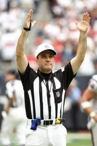 An NFL referee wearing the customary black and white striped shirt along with a white hat and white pants and his yellow penalty flag and blue fumble bag on his belt