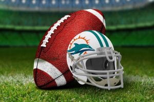 A white Miami Dolphins helmet featuring the teal dolphin, teal stripe, orange splash, and white facemask next to a football