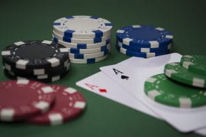 Stacks of poker chips on a pair of Aces on the green felt of a poker table to represent online gambling.