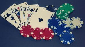 A Royal Flush in clubs on the blue felt of a poker table with poker chips to represent online poker bonuses.