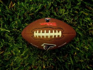 An NFL football with the black and red Atlanta Falcons logo lying on the green turf.
