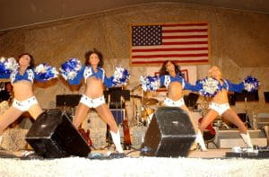 Dallas Cowboy cheerleaders in white shorts and white and blue blouses with white and blue pompoms dancing with an American flag in the background.