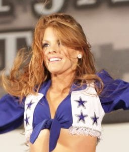 A Dallas Cowboys cheerleader wearing a blue and white blouse tied in the front featuring the Cowboys star logos.