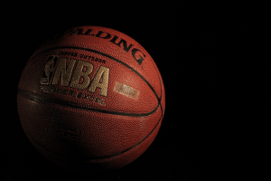 An official NBA orange leather basketball with gold lettering and a black backdrop.