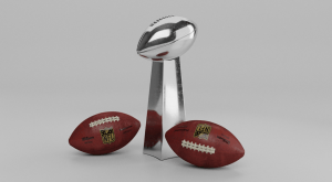 The silver Lombardi Trophy awarded to the Super Bowl Champion with two brown official NFL footballs by its side