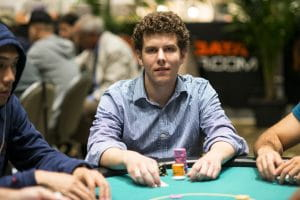 Ari Engel sitting on a poker table