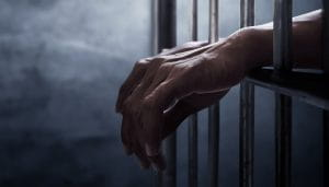 Person's Hands Behind Bars Over a Dark Background