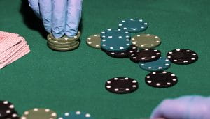 Casino Chips Handled with Gloves Next to Casino Cards on a Poker Table