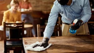 A Waiter with Mask and Gloves Cleaning a Table in a Caffee Using Detergent