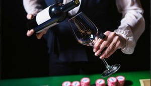 Casino Restaurant Staff Pooring Wine Over a Casino Table
