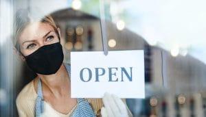 Seorang Asisten Toko yang Mengenakan Topeng Memegang Papan Bertuliskan Buka