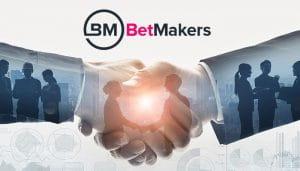 Logo BetMakers di atas Gambar Para Pengusaha Berjabat Tangan